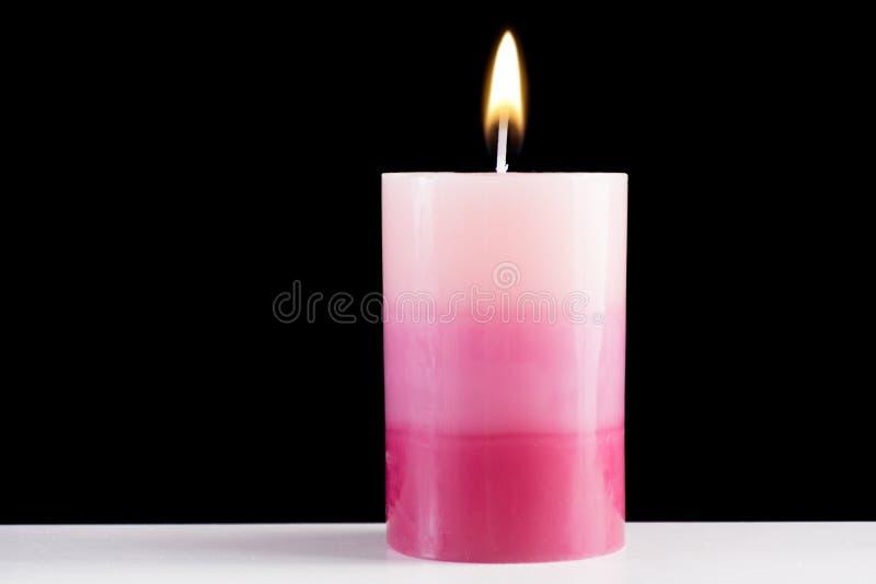 Πορφυρό ζωηρόχρωμο διακοσμητικό κάψιμο κεριών στο άσπρο γραφείο και το μαύρο υπόβαθρο στοκ εικόνα με δικαίωμα ελεύθερης χρήσης