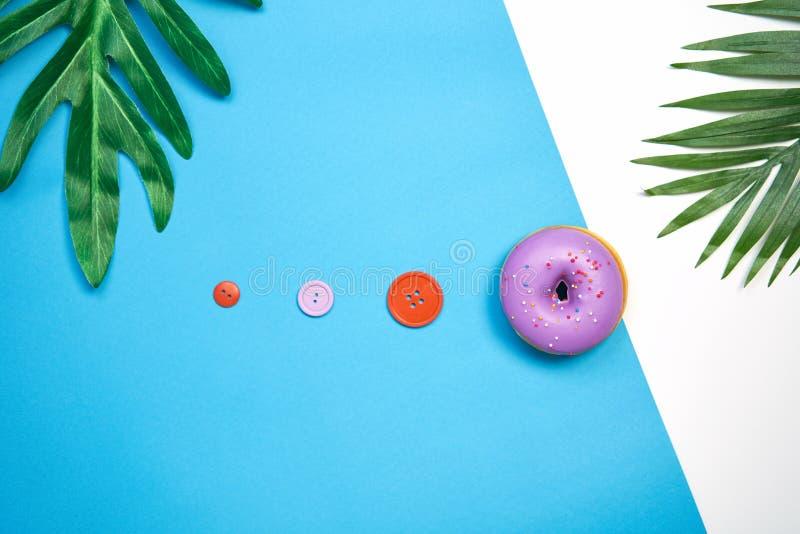 Πορφυρό doughnut και ζωηρόχρωμος σε ένα μπλε υπόβαθρο δημιουργικός μινιμαλισμός τροφίμων, κατάστημα καραμελών έννοιας στοκ φωτογραφία με δικαίωμα ελεύθερης χρήσης