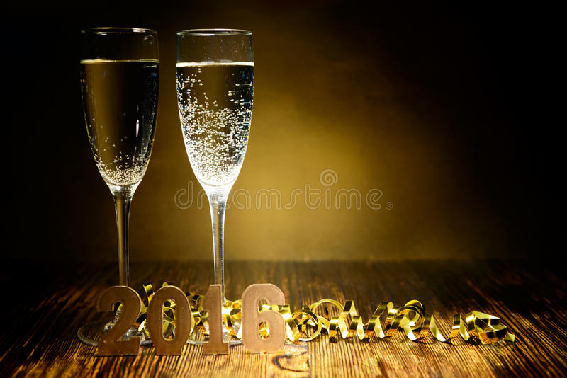 Ποτήρια της σαμπάνιας και των χρυσών σχημάτων 2016 για ένα ξύλινο backg στοκ φωτογραφία με δικαίωμα ελεύθερης χρήσης