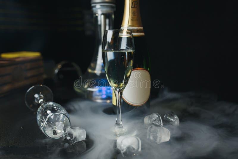 Ποτήρια της σαμπάνιας με το botlle και του πάγου στο μαύρο υπόβαθρο στοκ εικόνες