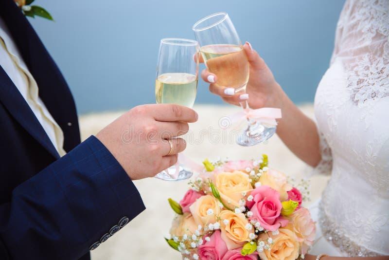 Ποτήρια της σαμπάνιας στα χέρια η νύφη και ο νεόνυμφος στη ημέρα γάμου στοκ εικόνες με δικαίωμα ελεύθερης χρήσης