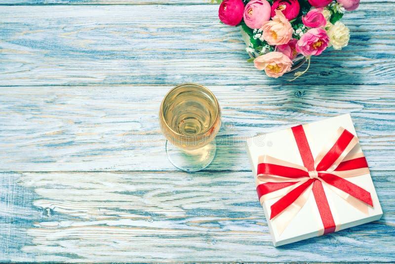 Ποτήρια του άσπρου κρασιού, των λουλουδιών και ενός δώρου στοκ φωτογραφία με δικαίωμα ελεύθερης χρήσης