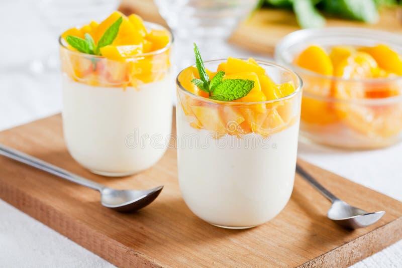 Ποτήρια του γιαουρτιού με το λαθραίο ροδάκινο στοκ φωτογραφίες