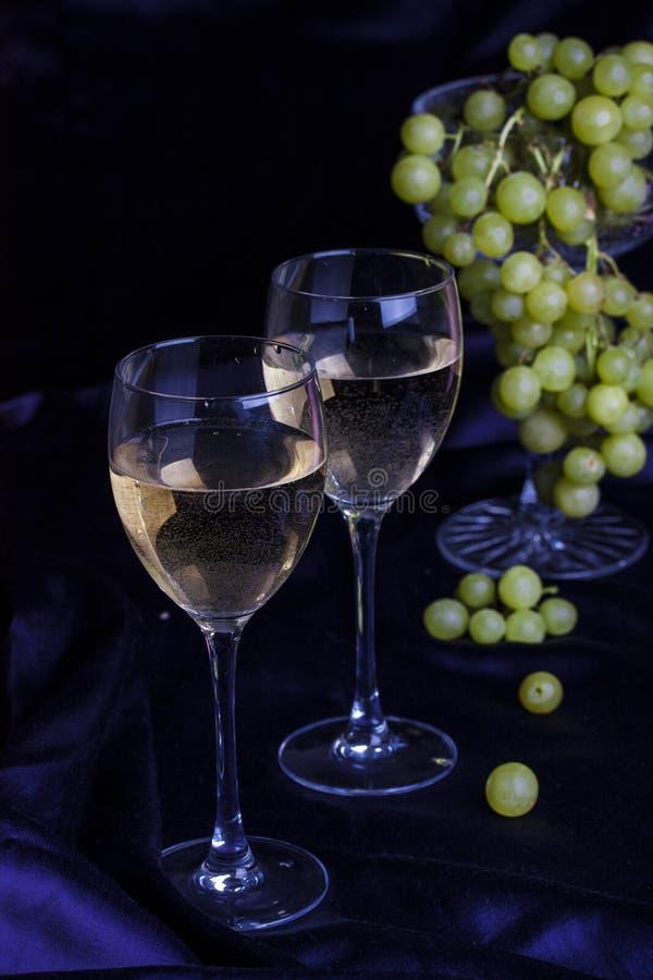 Ποτήρια του κρασιού και των σταφυλιών σε ένα σκοτεινό υπόβαθρο στοκ εικόνα