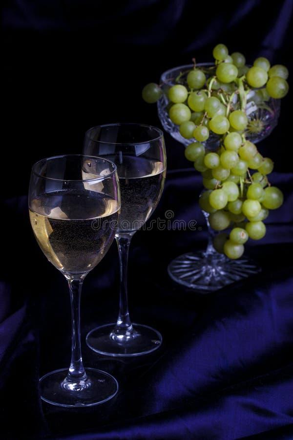 Ποτήρια του κρασιού και των σταφυλιών σε ένα σκοτεινό υπόβαθρο στοκ εικόνες