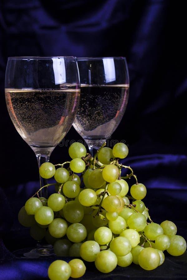 Ποτήρια του κρασιού και των σταφυλιών σε ένα σκοτεινό υπόβαθρο στοκ εικόνες με δικαίωμα ελεύθερης χρήσης