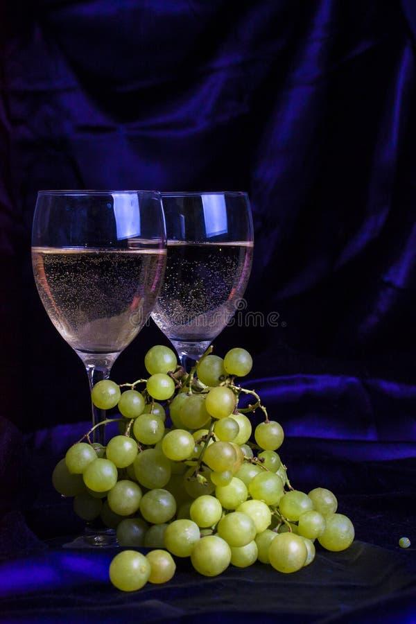 Ποτήρια του κρασιού και των σταφυλιών σε ένα σκοτεινό υπόβαθρο στοκ εικόνα με δικαίωμα ελεύθερης χρήσης