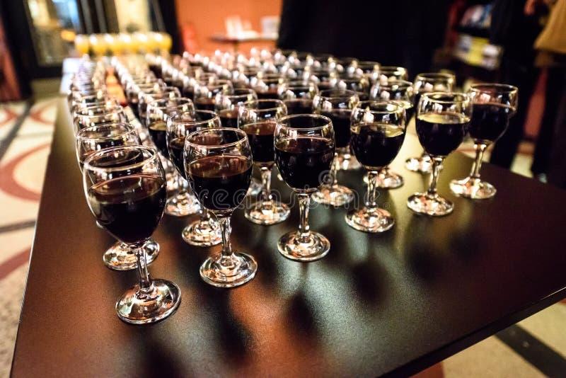 Ποτήρια του κόκκινου κρασιού σε έναν πίνακα σε ένα κόμμα στοκ εικόνες
