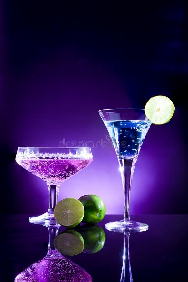 Ποτήρια του μπλε και πορφυρού κοκτέιλ με τον πράσινο ασβέστη στο φραγμό W στοκ φωτογραφία