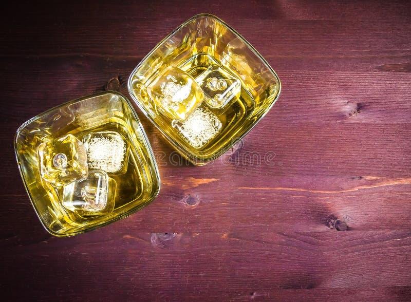 Ποτήρια του ουίσκυ με τον πάγο στον ξύλινο πίνακα στοκ εικόνα