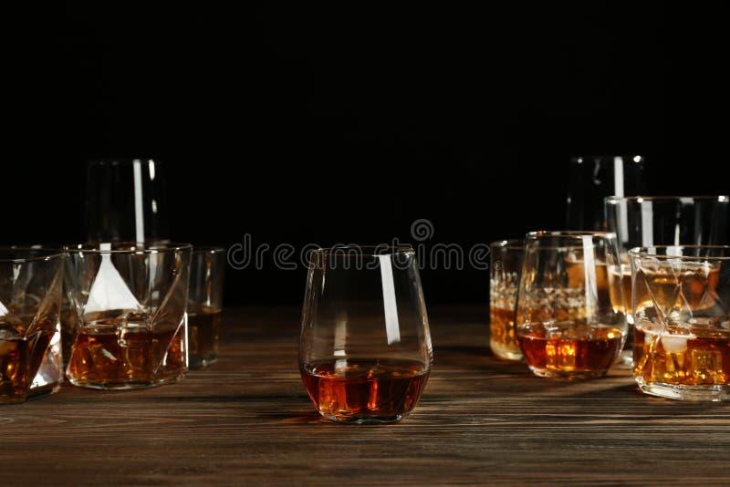 Ποτήρια του ουίσκυ στον ξύλινο πίνακα στο μαύρο κλίμα στοκ εικόνα με δικαίωμα ελεύθερης χρήσης