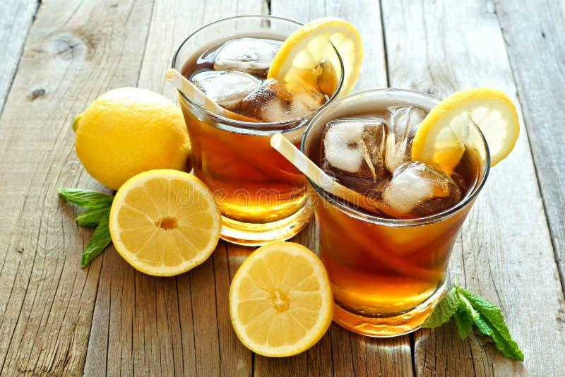 Ποτήρια του παγωμένου τσαγιού με τις φέτες λεμονιών στο αγροτικό ξύλο στοκ εικόνες