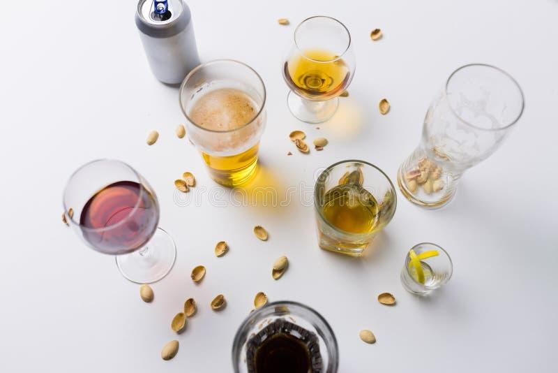 Ποτήρια των διαφορετικών ποτών οινοπνεύματος στον ακατάστατο πίνακα στοκ φωτογραφίες