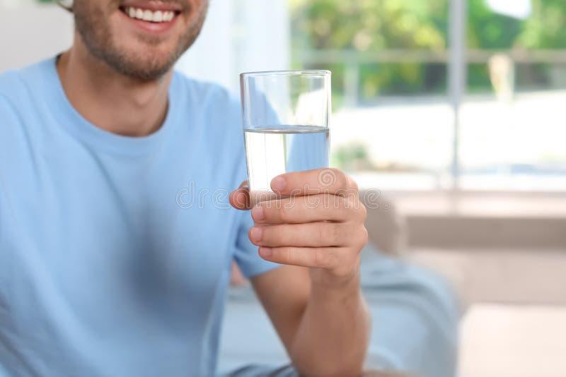Ποτήρι εκμετάλλευσης νεαρών άνδρων του καθαρού νερού στο εσωτερικό στοκ φωτογραφία με δικαίωμα ελεύθερης χρήσης