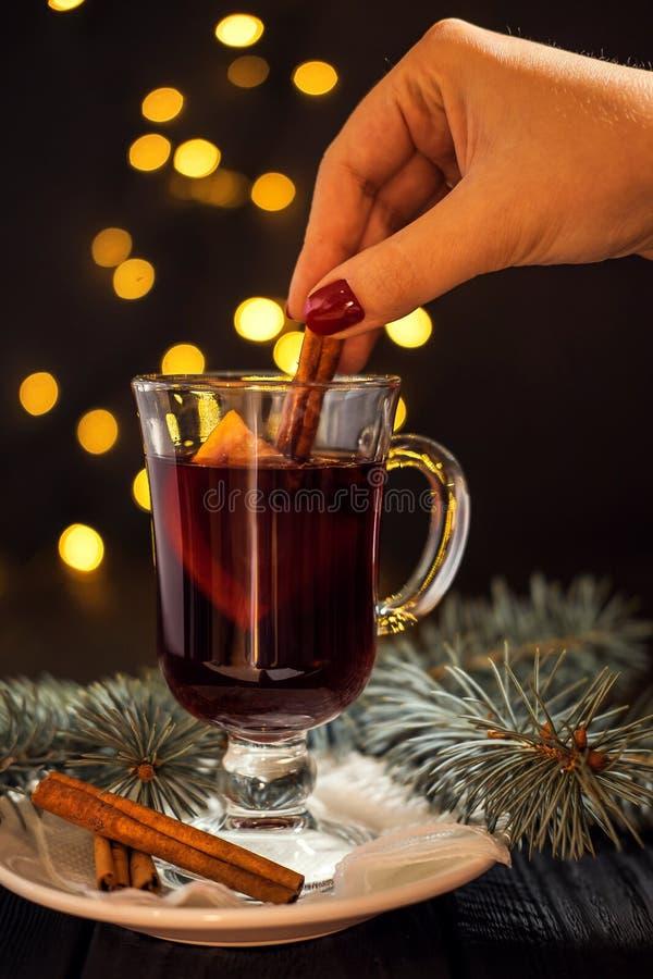 Ποτήρι κινηματογραφήσεων σε πρώτο πλάνο του θερμαμένου κρασιού με το πορτοκάλι και της κανέλας στο χέρι γυναικών στοκ εικόνες με δικαίωμα ελεύθερης χρήσης