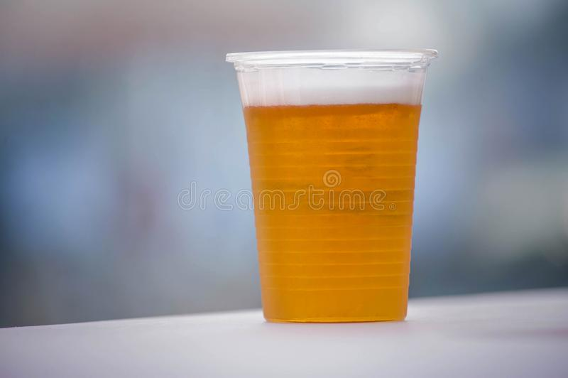 Ποτήρι της μπύρας σε ένα πλαστικό φλυτζάνι στοκ εικόνες