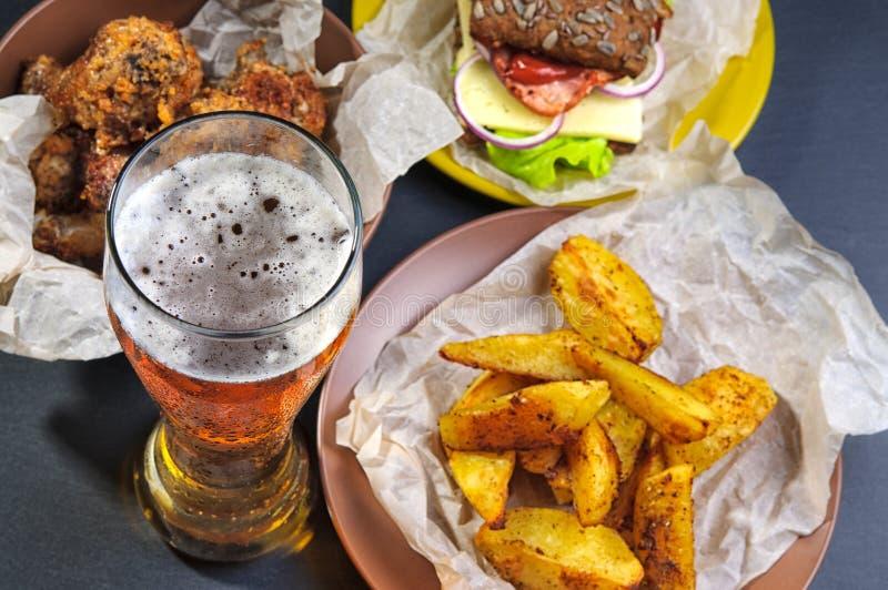 Ποτήρι της μπύρας, των τηγανητών, των ποδιών σάντουιτς και κοτόπουλου στοκ φωτογραφίες