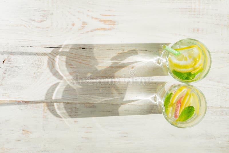 Ποτήρι της σπιτικής λεμονάδας με τα λεμόνια, τα άχυρα μεντών και εγγράφου στο ξύλινο αγροτικό υπόβαθρο Θερινό αναζωογονώντας ποτό στοκ φωτογραφία με δικαίωμα ελεύθερης χρήσης