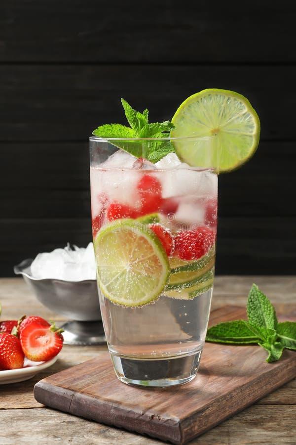 Ποτήρι της φυσικής λεμονάδας με τον ασβέστη, τις φράουλες και τη μέντα στον πίνακα στοκ φωτογραφία