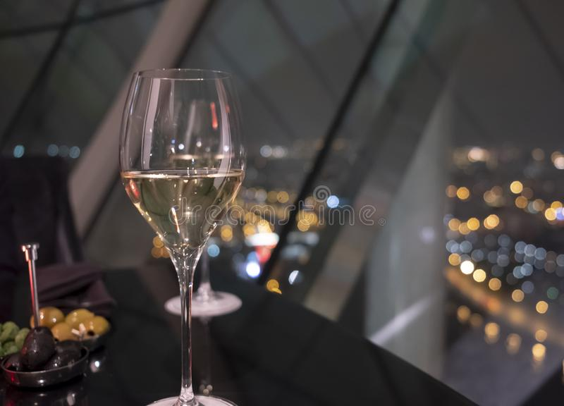 Ποτήρι του άσπρου κρασιού σε έναν μαύρο πίνακα στο εστιατόριο Η πόλη νύχτας ανάβει bokeh μέσω των πανοραμικών παραθύρων στο υπόβα στοκ εικόνες με δικαίωμα ελεύθερης χρήσης