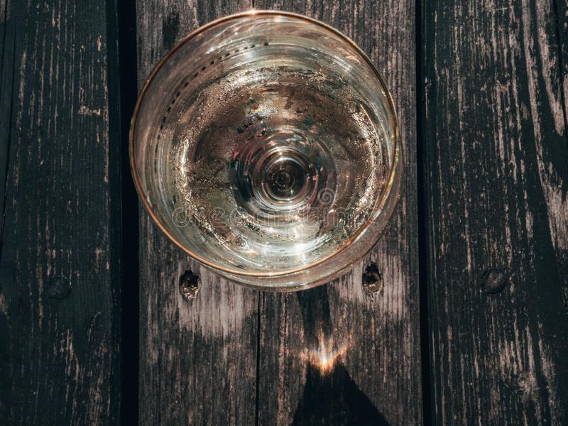 Ποτήρι του άσπρου κρασιού στον εκλεκτής ποιότητας ξύλινο πίνακα στοκ εικόνες