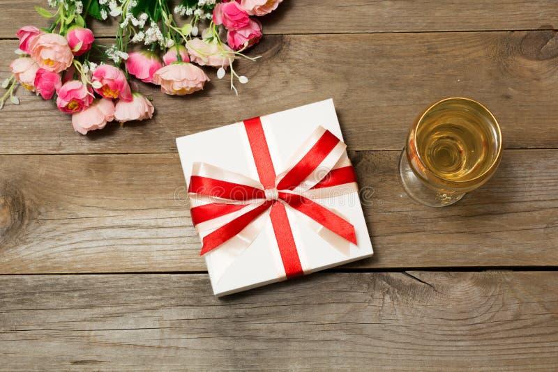 Ποτήρι του άσπρου κρασιού, των λουλουδιών και ενός δώρου στοκ φωτογραφία με δικαίωμα ελεύθερης χρήσης