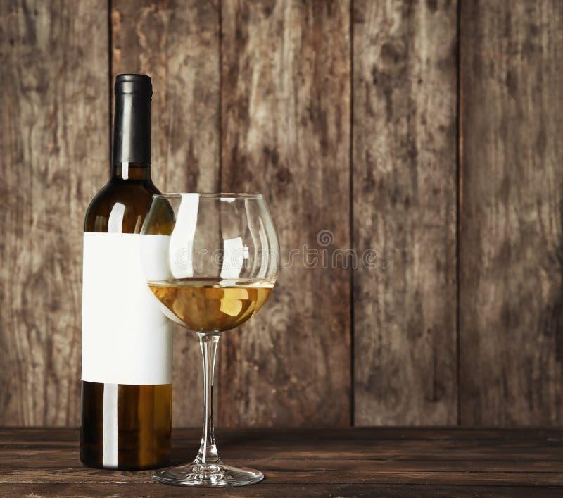 Ποτήρι του άσπρων κρασιού και του μπουκαλιού με την κενή ετικέτα στοκ εικόνα με δικαίωμα ελεύθερης χρήσης