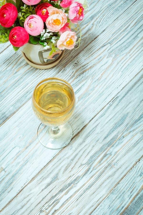 Ποτήρι του άσπρων κρασιού και των λουλουδιών στοκ εικόνα