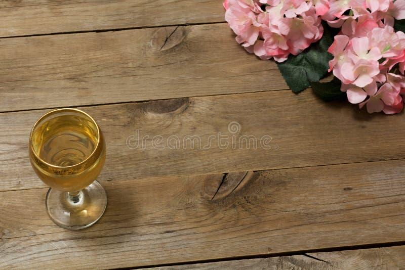 Ποτήρι του άσπρων κρασιού και των λουλουδιών στοκ εικόνες