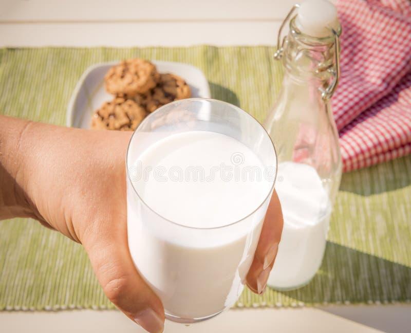 Ποτήρι του γάλακτος που κρατιέται υπό εξέταση στοκ εικόνες με δικαίωμα ελεύθερης χρήσης