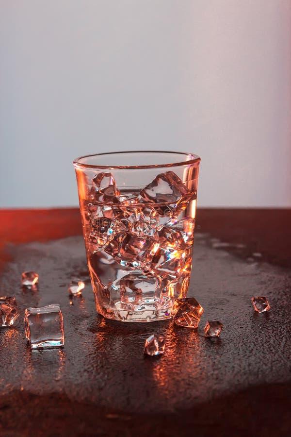 Ποτήρι του καθαρού νερού με τους κύβους πάγου Αφηρημένο δυναμικό σκηνικό για το σχέδιό σας στοκ φωτογραφία