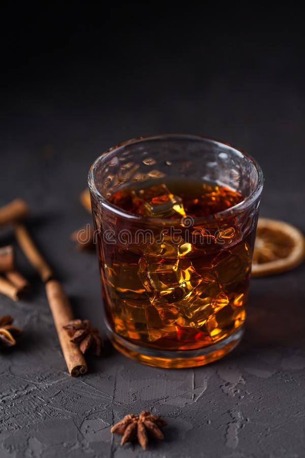 Ποτήρι του κονιάκ ή του ουίσκυ, καρυκεύματα και διακοσμήσεις στο σκοτεινό υπόβαθρο E στοκ εικόνες με δικαίωμα ελεύθερης χρήσης