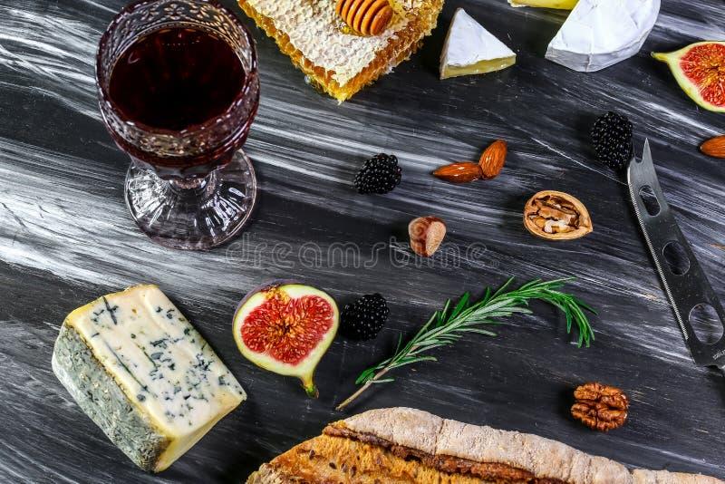 Ποτήρι του κόκκινου κρασιού και του τυριού με το moldy τυρί κομματιών, prosciutto, σύκα, μέλι, καρύδια στο μαύρο υπόβαθρο πλακών στοκ φωτογραφίες