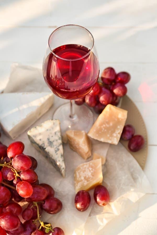 Ποτήρι του κόκκινου κρασιού με το τυρί και των φρέσκων σταφυλιών στον ελαφρύ πίνακα στοκ εικόνες