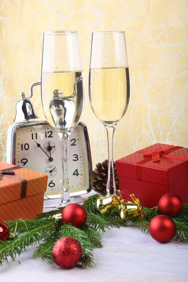 Ποτήρι του λαμπιρίζοντας shampagne κρασιού, του ρολογιού, του κιβωτίου δώρων και των κεριών στο υπόβαθρο Χριστουγέννων στοκ φωτογραφία με δικαίωμα ελεύθερης χρήσης