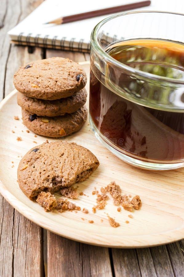 Ποτήρι του μαύρου καφέ με τα μπισκότα τσιπ σοκολάτας στο ξύλινο plat στοκ εικόνες με δικαίωμα ελεύθερης χρήσης