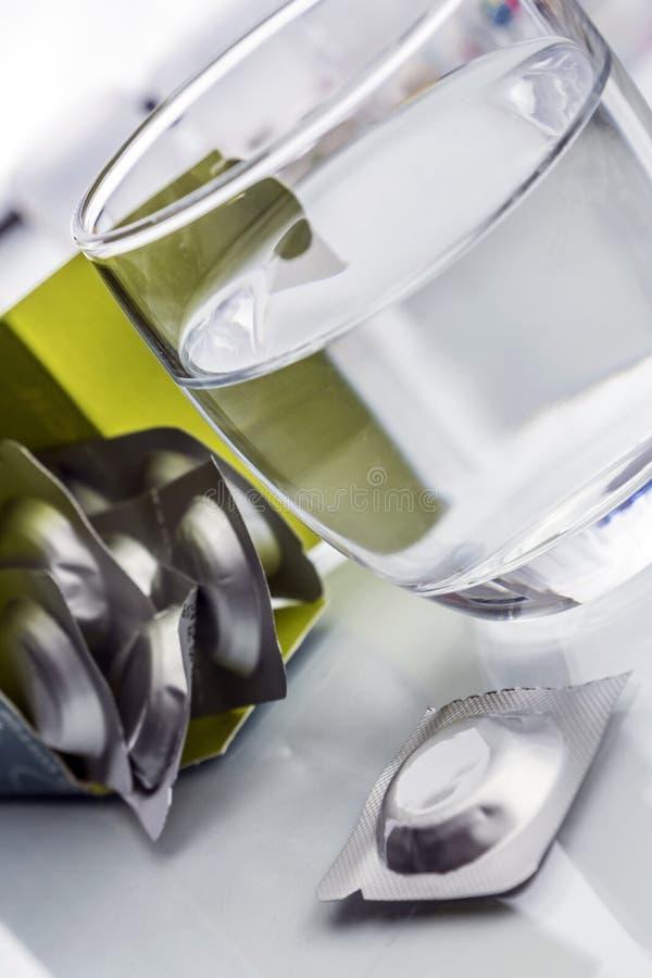 Ποτήρι του νερού δίπλα σε ένα ζωηρό χάπι στοκ εικόνες με δικαίωμα ελεύθερης χρήσης