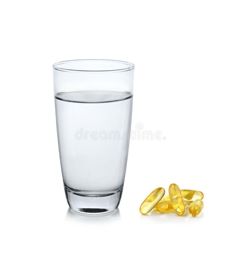 Ποτήρι του νερού με το πετρέλαιο ψαριών στο άσπρο υπόβαθρο στοκ φωτογραφία