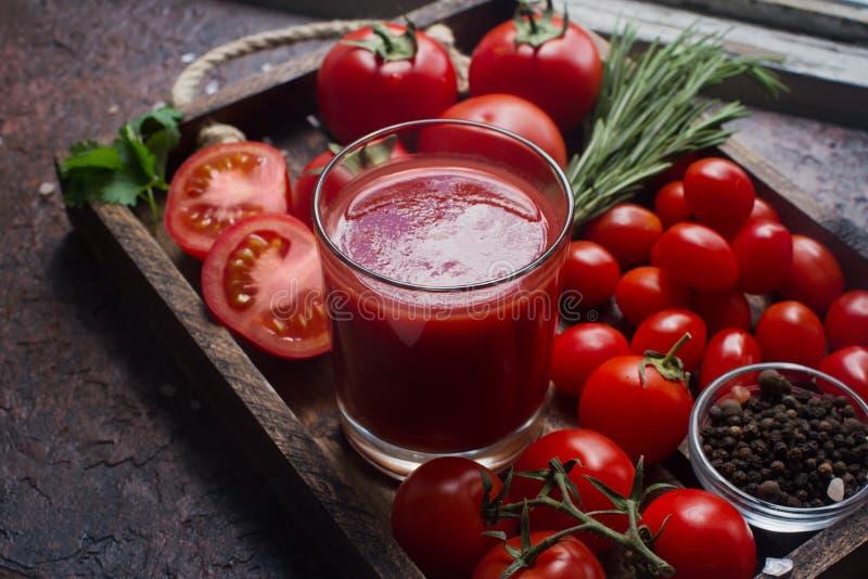 Ποτήρι του νόστιμου οργανικού χυμού ντοματών και των φρέσκων ντοματών και χορτάρια στον ξύλινο δίσκο στο αγροτικό ύφος στοκ εικόνα με δικαίωμα ελεύθερης χρήσης