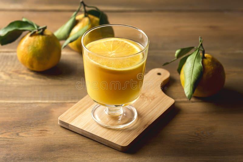 Ποτήρι του νόστιμου χυμού εσπεριδοειδών που αναζωογονεί Tangerin χυμού από πορτοκάλι το ξύλινο ποτό Detox υποβάθρου υγιές στοκ εικόνες