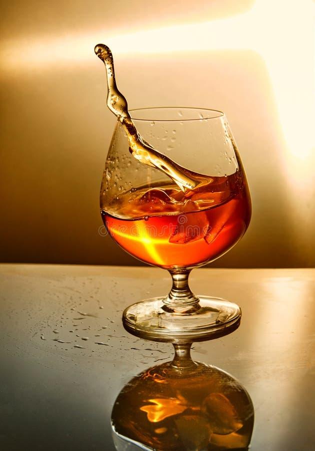 Ποτήρι του ουίσκυ με ένα κύμα σε ένα πορτοκαλί υπόβαθρο στοκ εικόνα με δικαίωμα ελεύθερης χρήσης
