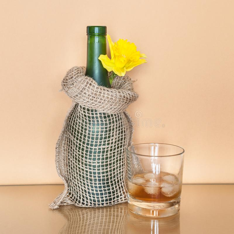 Ποτήρι του ουίσκυ με τον πάγο και ενός μπουκαλιού που τυλίγεται στη διακοσμητική τσάντα καμβά στοκ εικόνα