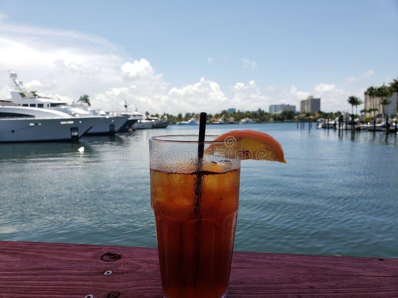 Ποτήρι του παγωμένου ποτού τσαγιού κοντά στη μαρίνα με τις βάρκες στοκ εικόνες