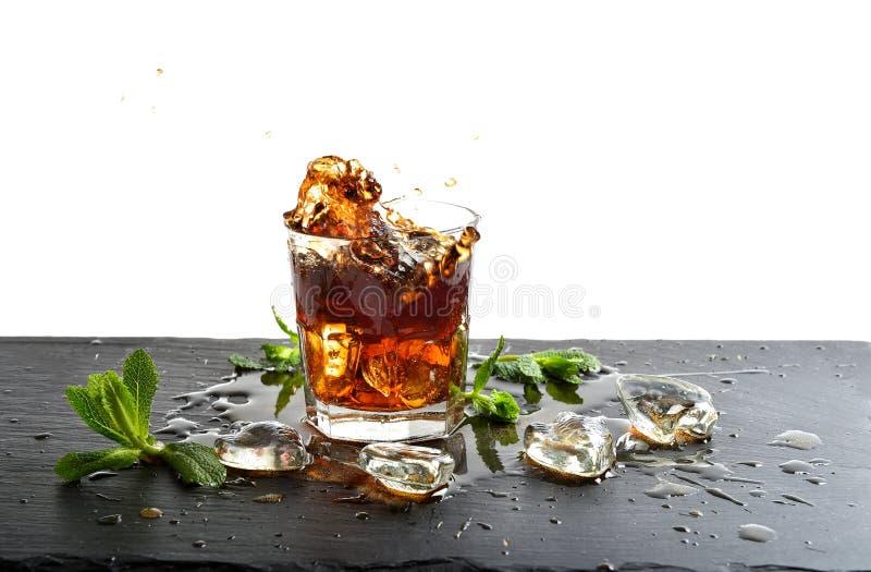 Ποτήρι του ποτού κόλας με τα φύλλα πάγου και μεντών στοκ φωτογραφία