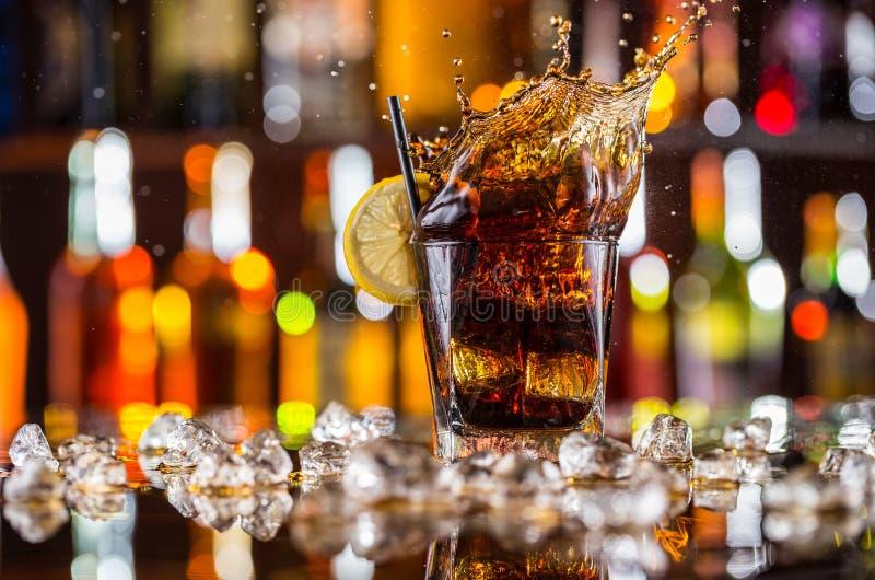 Ποτήρι του ποτού κόλας με τον παφλασμό στο μετρητή φραγμών στοκ εικόνες με δικαίωμα ελεύθερης χρήσης
