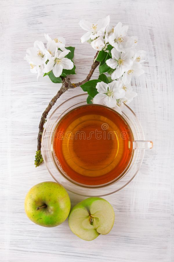Ποτήρι του τσαγιού με το φρέσκο ώριμο πράσινο μήλο που διακοσμείται με το όμορφο άνθος μήλων στον άσπρο ξύλινο πίνακα στοκ εικόνες
