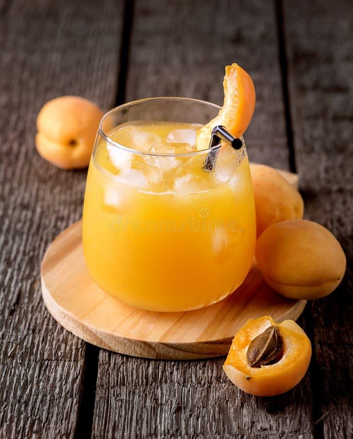 Ποτήρι του φρέσκου νόστιμου χυμού βερίκοκων στο ξύλινο ποτό διατροφής υποβάθρου κάθετο υγιές στοκ εικόνα