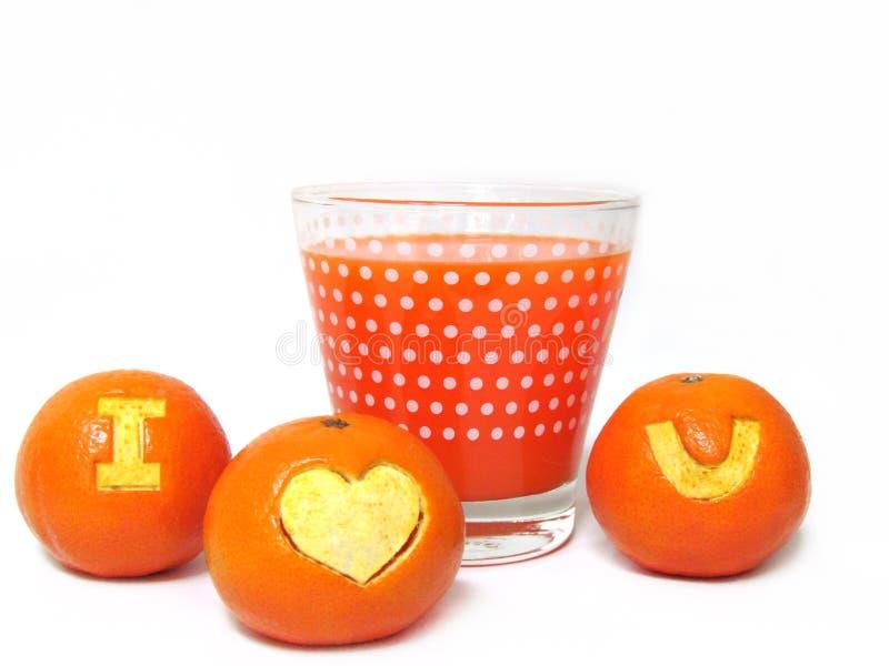 """Ποτήρι του χυμού από πορτοκάλι και του φρέσκου πορτοκαλιού που χαράζουν ένα σύμβολο """"I Lov στοκ εικόνες με δικαίωμα ελεύθερης χρήσης"""