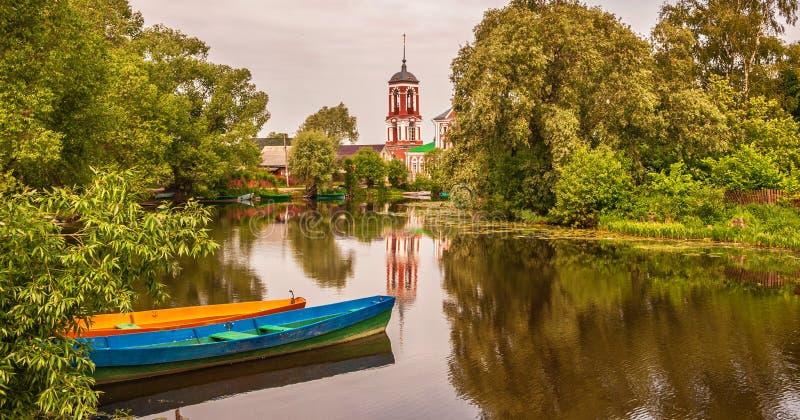Ποταμός, βάρκα και εκκλησία στην ακτή στοκ φωτογραφία με δικαίωμα ελεύθερης χρήσης