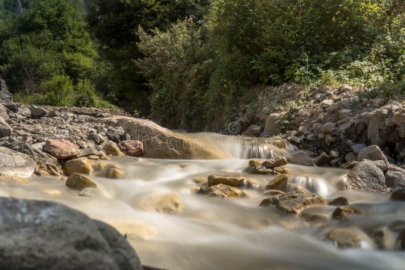 Ποταμός βουνών με το γρήγορο ρεύμα και με τα φωτεινά θολωμένα κύματα Μεγάλοι mossy λίθοι στο σαφές νερό στοκ φωτογραφίες